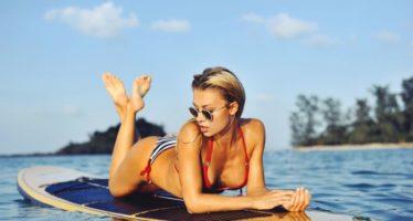 Sexy female model on surfboard in sea
